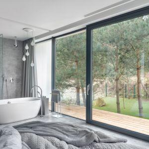 Widoczny z łazienki świerkowy las, dzięki dużym przeszkleniom śmiało wkracza do wnętrza. W ten sposób pokój kąpielowy otwiera się na otaczającą dom przyrodę. Projekt: Aleksandra Mierzwa, Wiktor Kurc (Maka Studio). Fot. Tom Kurek