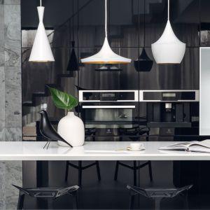 Bazę kuchennej przestrzeni stanowi czarna drewniana wyspa z prostym corianowym blatem. Projekt: Aleksandra Mierzwa, Wiktor Kurc (Maka Studio). Fot. Tom Kurek