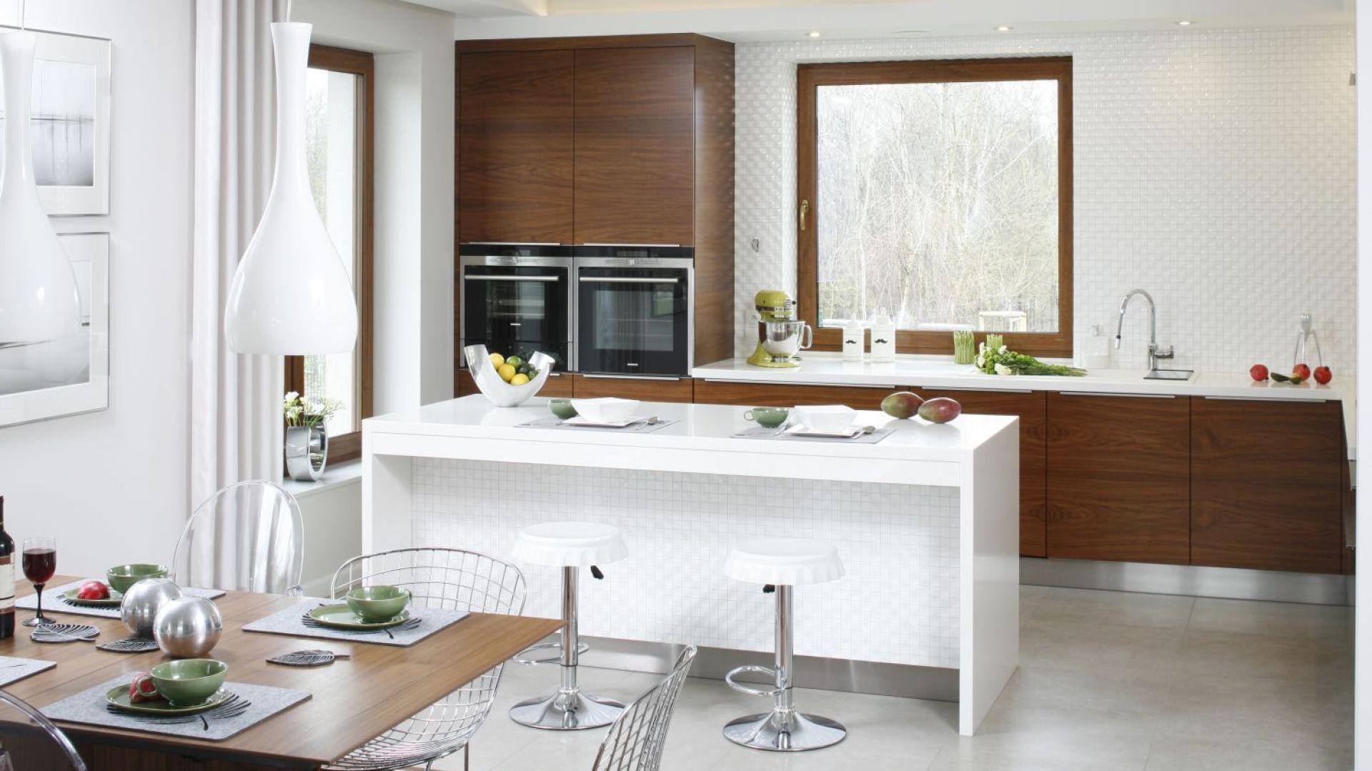 Biel i drewno dominują również w strefie kuchni. Projekt Piotr Stanisz. Fot. Bartosz Jarosz