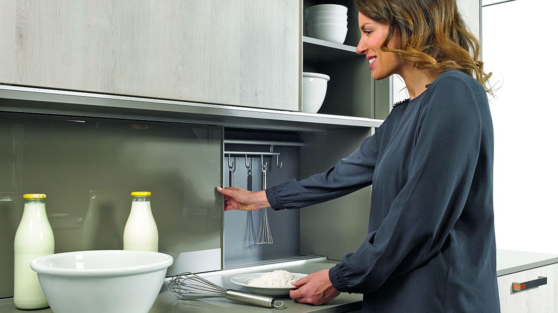 System Slideline M do przesuwnych drzwi wpuszczanych, umożliwia przechowywanie akcesoriów kuchennych, na które nie mamy miejsca w szafkach lub nie chcemy ich trzymać na widoku. Jednym ruchem dłoni delikatnie przesuwamy front, ukrywając zawartość schowka. Dostępny w ofercie firmy Hettich. Fot. Hettich