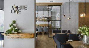 W projekcie restauracji WhiteOne wykorzystano wiele nowatorskich pomysłów. Architekci w nawiązaniu do historii miejsca, posłużyli się drewnem, pochodzącym z bali przedwojennej kamiennicy, która sąsiaduje z restauracją.