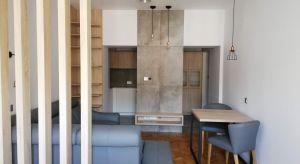 Pierwotnie kuchnia w tej krakowskiej kawalerce stanowiła oddzielne, maleńkie pomieszczenie, w którym mieściła się jedynie kuchenka, lodówka i zlewozmywak. Funkcję blatu roboczego pełnił niewielki stolik.