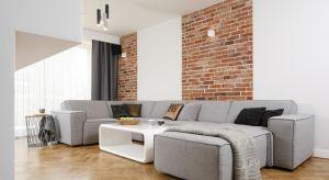W przestronnym salonie w doskonałej aranżacyjnej symbiozie występuje drewno w formie parkietu na podłodze, rozbiórkowa cegła oraz modne, nowoczesne wyposażenie.