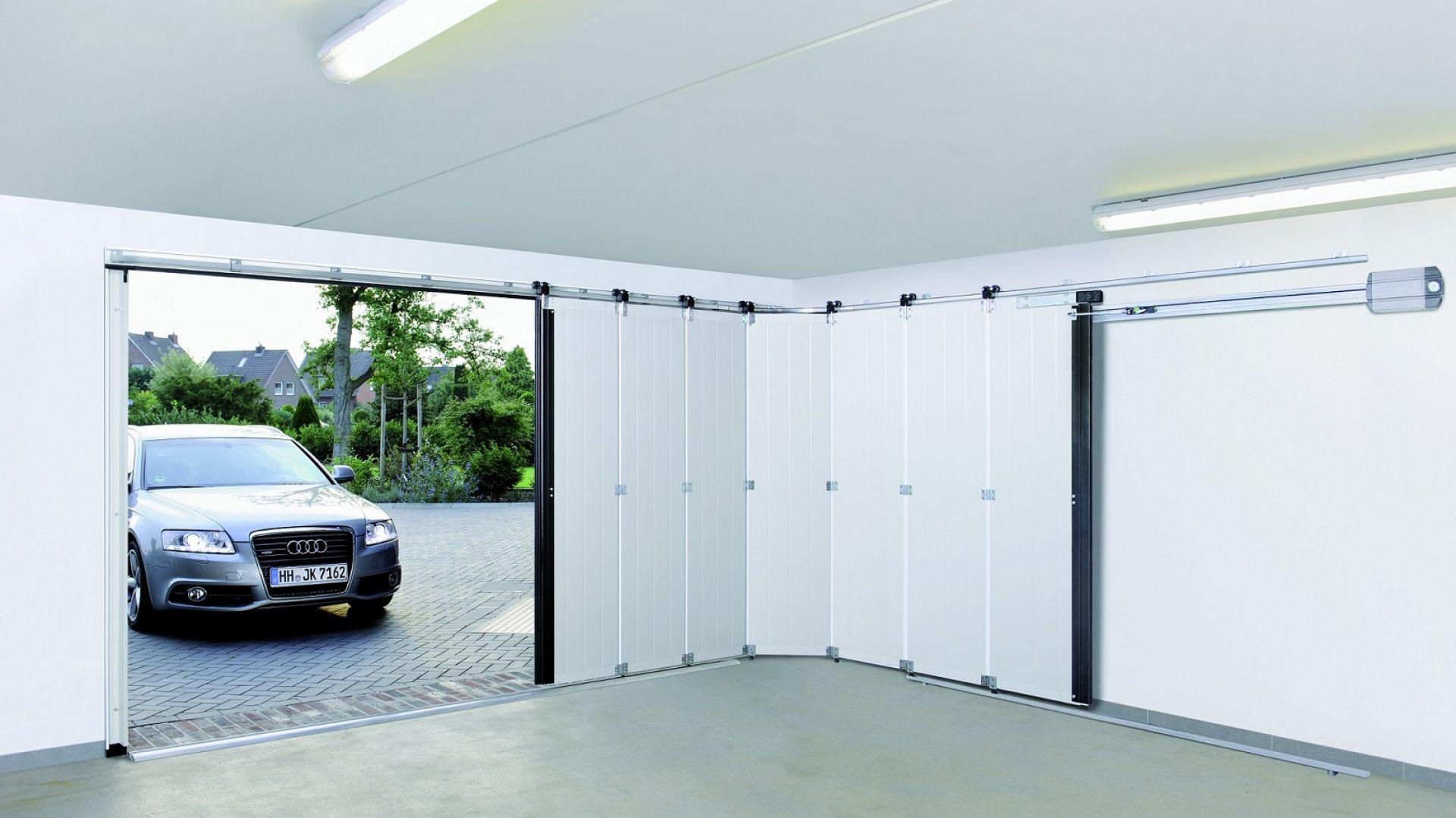Urządzamy garaż - brama garażowa boczna HST. Brama otwiera się na bok i stanowi alternatywę dla zwykłej konstrukcji segmentowej w trudnych sytuacjach montażowych. Bardzo dobrze sprawdza się, gdy chcemy zachować wolne miejsce pod sufitem, a także w garażach o niskim nadprożu. Fot. Hörmann
