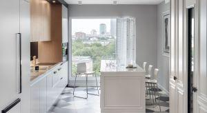 W tej kuchni naprzeciw siebie stanęły klasyka i nowoczesność. Ito dosłownie. Większa część zabudowy przy ścianie ma nowoczesny charakter.Natomiast styl wyspy oraz szafy z winiarką, znajdujących się po przeciwnej stronie, jest zdecydowanie