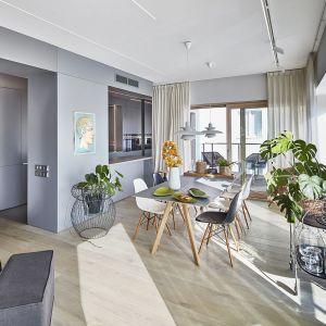 Główną częścią mieszkania jest salon z otwartą kuchnią, gdzie najbardziej przykuwają wzrok trzy ściany z dużymi oknami, wychodzącymi na przeszklony taras. Projekt:  81.waw.pl. Fot. Budzik Studio