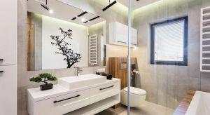 W tej przestronnej łazience prym wiodą proste linie i naturalne materiały. Króluje drewno, szkło i beton.