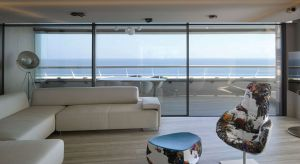 Wielkoszybowe okna i system przesuwnych drzwi tarasowych sprawiają, że granica między wnętrzem apartamentu a tarasem jest praktycznie niezauważalna. W ten sposób mieszkanie otwarto też na niesamowity widok na Morze Śródziemne.