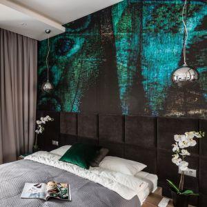 Tapeta z motywem pawiego pióra to główny akcent tej sypialni. Jej aksamitna faktura doskonale harmonizuje z tapicerowanym panelem na ścianie za łóżkiem. Projekt: Studio Projekt. Fot. Fotomohito