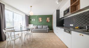 Główny element, który zwraca uwagę w apartamencie to ciemnooliwkowa ściana w salonie. Wzbogacona elementami sztukaterii stała się atrakcyjnym tłem do prezentacji galerii obrazów i geometrycznych luster w złotych ramach.