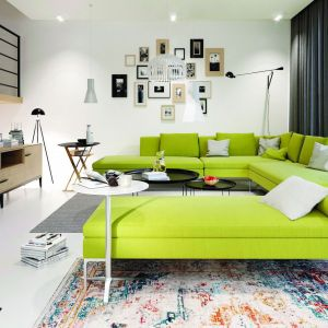 Jasnozielona kanapa, soczyście pomarańczowy fotel i dużo naturalnego światła - w takim salonie nie sposób długo się smucić. Projekt: Artur Wójciak. Fot. Pracownia Projektowa Archipelag