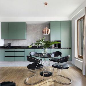 Otwarta na salon zabudowa kuchni w nietypowym zielonym kolorze wybija się zdecydowanie na pierwszy plan całej przestrzeni. Projekt: studioLOKO, Fot. Karolina Chęcińska