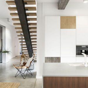 Dekory inspirowane drewnem na frontach mebli kuchennych doskonale komponują się z białym blatem, który stanowi dla nich neutralne tło i podkreśla walory estetyczne. Fot. Pfleiderer