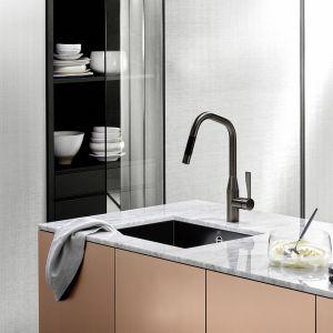 Jasny marmurowy blat wyraźnie kontrastuje z matowym zlewozmywakiem z glazurowanej stali oraz baterią Sync w wykończeniu Dark Platinum matt. Fot. Dornbracht
