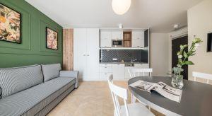 Pierwszym z elementów, na które zwracamy uwagę w apartamencie, jest ciekawa kolorystyka jednej ze ścian w salonie. Zastosowana tu ciemnooliwkowa zieleń wprowadza do wnętrza spokój, dodając przestrzeni elegancji.