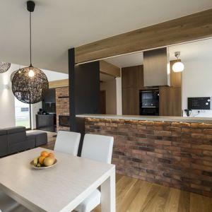 Oddzielający kuchnię od jadalni bar obłożono naturalną cegłą. Ten sam materiał pojawia się też przy kominku w salonie. Projekt i zdjęcie: Katarzyna Benko (Och-Ach Concept)