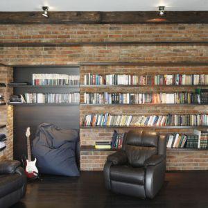 Tu cegła gra pierwsze skrzypce. Ścianę wykończoną cegłą wykorzystano jako biblioteczkę. Projekt: Izabela Mildner. Fot. Bartosz Jarosz