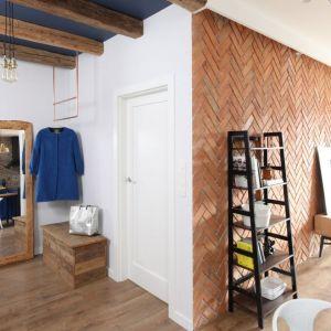 Cegła, oryginalnie ułożona w jodełkę na ścianie oraz drewniane belki pod sufitem dodają przytulności temu niewielkiemu mieszkaniu. Projekt: Anna Krzak. Fot. Bartosz Jarosz