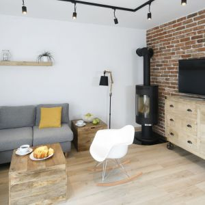 W niewielkim salonie uwagę zwraca stolik kawowy w formie prostopadłościanu z prostych drewnianych desek. Projekt: Katarzyna Uszok. Fot. Bartosz Jarosz