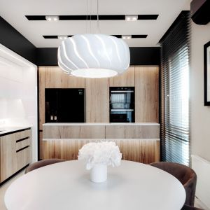 Motywem przewodnim aranżacji mieszkania są drewniane fronty mebli połączone z elegancką bielą i podkreślone czarnymi detalami. Projekt i zdjęcia: Eliza Polakiewicz / EP Studio