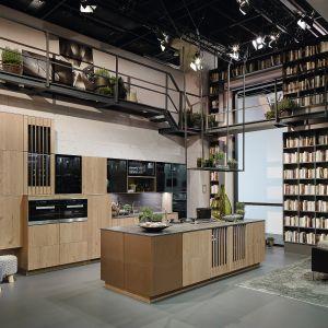 Kuchnia z systemu Alnoattract łączy urok drewna z nowoczesną stylistyką. Nieregularny kształt wysokiej zabudowy nadaje jej niepowtarzalny wygląd. Dostępna w ofercie firmy Alno. Fot. Alno