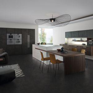 Wysoka zabudowa meblowa w kuchni Topos|Concret oferuje dwa słupki na urządzenia AGD oraz dwie dwudrzwiowe szafy: w jednej ukryta jest strefa robocza z praktycznym blatem i szufladami. Dostępna w ofercie firmy Leicht. Fot. Leicht