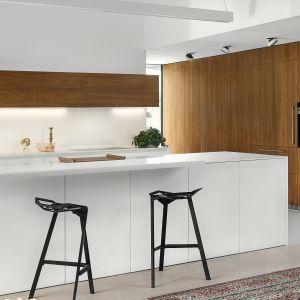 Chłodne, minimalistyczne wykończenia wyspy w kuchni Z1 kontrastuje z wysoką zabudową wykończoną fornirem orzechowym. Pionowy układ słojów na wysokich szafach optycznie je wydłuża. Dostępna w ofercie firmy Zajc. Fot. Zajc
