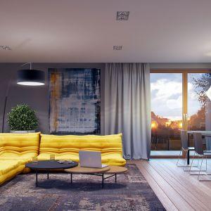 W prezentowanej aranżacji salonu króluje słynna sofa Togo. Jej energetyczny, żółty kolor doskonale pasuje do nowoczesnego charakteru wnętrza, efektownie łącząc modny design z przytulnością. Dom Marcel G2. Projekt: arch. Artur Wójciak, Pracownia Projektowa Archipelag