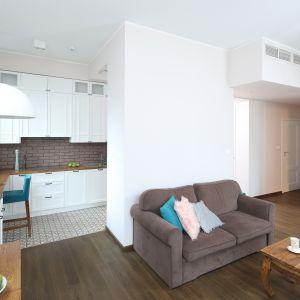 Kuchnia od strefy wypoczynkowej oddziela niepełna ścianka. Obie przestrzenie wyznacza też inny rodzaj  materiału podłogowego. Projekt: Ola Kołodziej, Ula Szmyt. Fot. Bartosz Jarosz