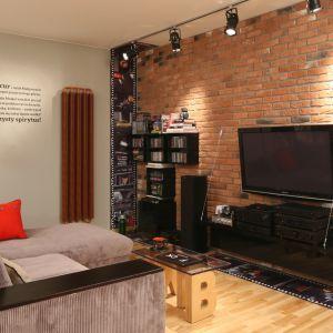 Wnętrze w stylu loft: czerwona cegła na ścianie salonu dodaje charakteru. Projekt: Iza Szewc. Fot. Bartosz Jarosz