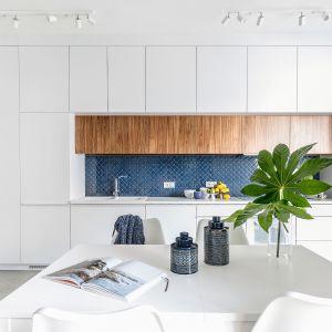 Pojemne meble poprowadzone od podłogi aż po sam sufit zapewniają dużo miejsca do przechowywania. Projekt: Monika Pniewska. Fot. Marta Behling/Pion Poziom