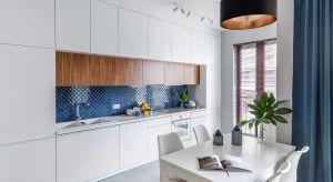 Pojemna zabudowa kuchenna w klasycznej kolorystyce okala wkomponowaną w nią ścianę nad blatem. Ta z kolei wyróżnia się intensywną, kobaltową barwą i pięknym, arabeskowym wzorem.