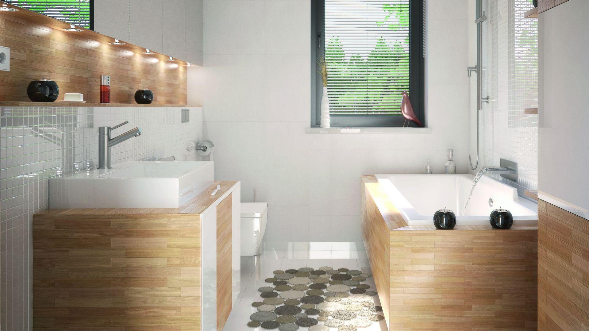 W łazience dominuje biel i drewno, co sprawia, że wnętrze jest przestronne i estetyczne. Dom Umbra. Projekt: arch. Maciej Matłowski. Fot. Domy w Stylu