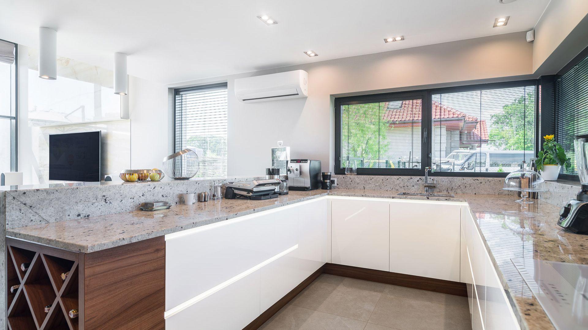 Blat oraz półwysep w kuchni zostały wykonane z granitu kashmir white. Źródło: Dekorian Home. Projekt: Marta Sergiej. Fot. Wojciech Dziadosz