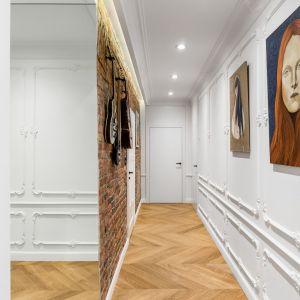 W tym przypadku białe ściany ozdobione sztukaterią pozwoliły wyeksponować kolekcję obrazów. Dla kontrastu, jedną ze ścian wykończono starą cegłą umiejętnie łącząc różne style. Projekt: Anna Maria Sokołowska. Fot. Fotomohito