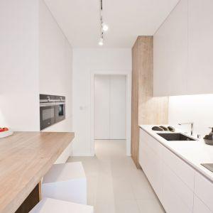 Przy wyborze opraw oświetleniowych w najważniejszych pomieszczeniach typu salon i kuchnia projektanci preferowali zdecydowany, dominujący element na suficie, czysty i prosty w formie. Efekt taki dają szynoprzewody. Projekt: Pracownia INTO. Fot. Fotobueno