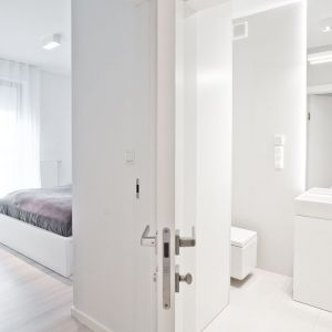 Sypialnia i wejście do sąsiadującej łazienki. Projekt: Pracownia INTO. Fot. Fotobueno