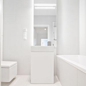 Nowoczesny kinkiet w łazience, dzięki równomiernemu świeceniu może komfortowo oświetlić twarz osoby stojącej przed lustrem. Projekt: Pracownia INTO. Fot. Fotobueno