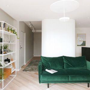 Mocnym akcentem kolorystycznym salonu jest sofa pokryta welurową tkaniną w kolorze butelkowej zieleni. Projekt: Aleksandra Pater-Bartnik. Fot. ArchOmega Studio