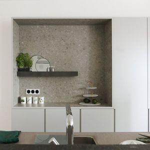 W minimalistyczną wysoką zabudowę wkomponowano kamienną wnękę. Projekt: Aleksandra Pater-Bartnik. Fot. ArchOmega Studio