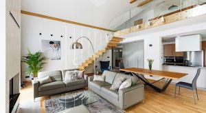 Wnętrze położonego pod Krakowem domu to połączenie nowoczesnej stylistyki i przytulnej atmosfery. Modernistyczne formy zestawiono tutaj z naturalnymi akcentami w postaci drewna w ciepłym wybarwieniu i kamienia.