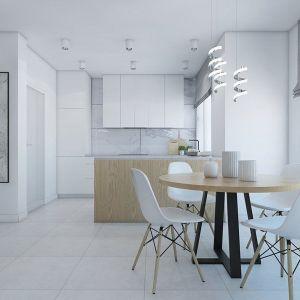 Ścianę w tej kuchni zabezpieczono wielkoformatowymi płytkami ceramicznymi do złudzenia przypominającymi pięknie żyłkowany marmur. Taka okładzina nie tylko dobrze chroni ścianę, ale i jest dużą ozdobą nowoczesnego wnętrza. Fot. Pracowni Projektowej MGN