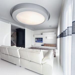 Dominuje tu styl minimalistyczny – biel i naturalne drewno królują w pomieszczeniach strefy dziennej. Salon urządzono funkcjonalnie, z dbałością o każdy szczegół. Wnętrze pozbawione jest zbędnych ozdobników i bibelotów. Rolę dekoracji pełnią tu eleganckie meble i nowoczesne oświetlenie. Fot. Biuro Projektów MTM Styl
