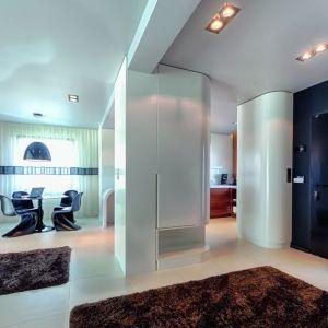 Centralnym miejscem parteru jest otwarta strefa dzienna, łącząca salon, jadalnię i kuchnię. Jedynym elementem dzielącym wnętrze jest kolumna konstrukcyjna. Całość uzupełniają nowoczesne, czarne meble w jadalni.  Fot. Biuro Projektów MTM Styl