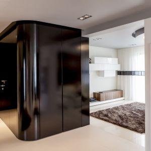 W holu szeroka zabudowa szafy jest błyszcząco czarna, co wyróżnia się na tle białych ścian i innych jasnych elementów wyposażenia. Fot. Biuro Projektów MTM Styl