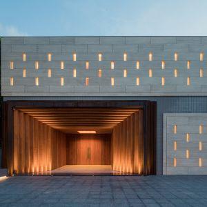 Fasada, na której znajduje się główne wejście, została pokryta płytami z jasnego trawertynu, w których wycięto perforacje do celów oświetlenia i wentylacji. Fot. Schüco
