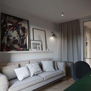 Na przeciwległej ścianie ustawiono sofę w jasnym beżowym kolorze, dzięki temu zneutralizowano nieco mocny kolor, tak aby nie przytłaczał niewielkiego wnętrza. Projekt i zdjęcia: JMW Architekci
