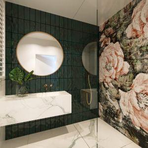 W drugiej łazience, gościnnej, na głównej ścianie położono płytki-kafelki Tonalite Krakle w kolorze mieniącej się różnymi odcieniami zieleni, a ściana pod prysznicem dostała dekoracyjną tapetę włoskiej marki Wall&Deco, w duże efektowne kwiaty. Projekt i zdjęcia: JMW Architekci