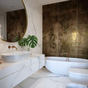 W prywatnej łazience połączonej bezpośrednio z sypialnią uwagę zwraca ściana za wanną wyłożona wielkoformatowymi płytami z postarzanego mosiądzu. Projekt i zdjęcia: JMW Architekci