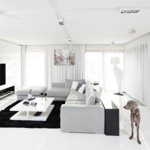 Niezwykle nowoczesny jasny salon. Biel i delikatny odcień szarości połączono tu z elegancką czernią. Projekt: Małgorzata Muc, Joanna Scott. Fot. Bartosz Jarosz